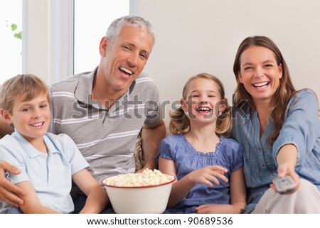 Family watching a movie in a living room - stock photo