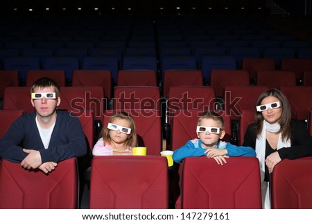 Family watching a movie in 3D cinema with popcorn - stock photo