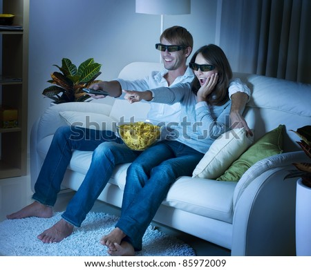 Family watching 3D film on TV - stock photo