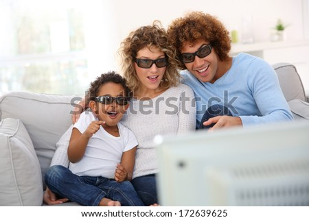 Family watching 3D movie on tv - stock photo