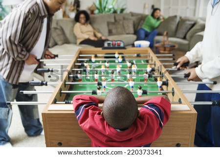Family watching foosball game - stock photo