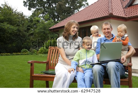 Family watching laptop on the bench in front of the house - stock photo