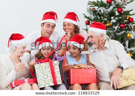 Family watching little girl opening christmas present on the couch - stock photo