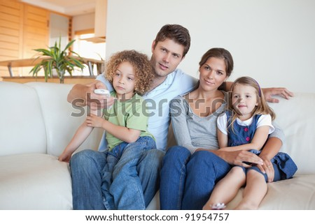 Family watching TV together in their living room - stock photo
