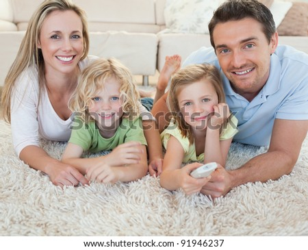Family watching tv together on the floor - stock photo