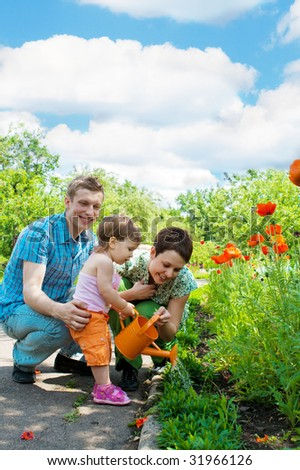 Family watering flowers in their garden - stock photo