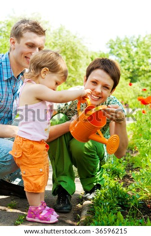 Family watering plants in the garden