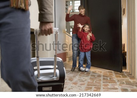Family waving goodbye to father leaving for a trip - stock photo