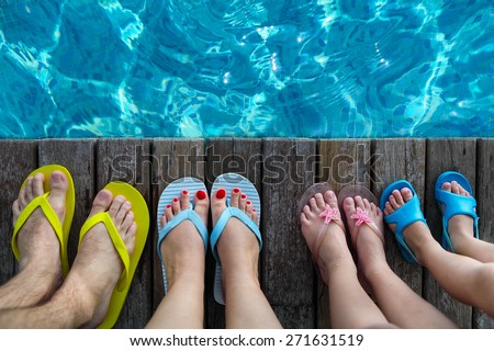 Family wearing brightly colored flip-flops on wooden background near the pool. Summer travel and vacation concept - stock photo