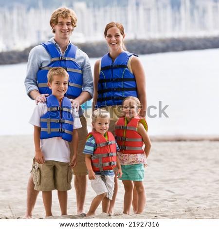 Family wearing life jackets at beach - stock photo