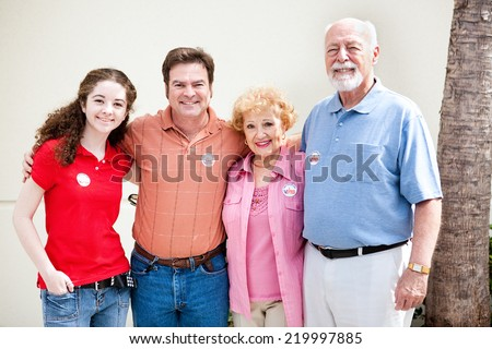 Family wearing their I Voted stickers on election day.  (stickers are generic, not trademarked) - stock photo