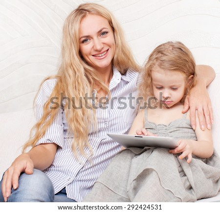 Family wiht tablet at sofa. Woman and baby with tablet computer. Mother and daughter at home on sofa - stock photo