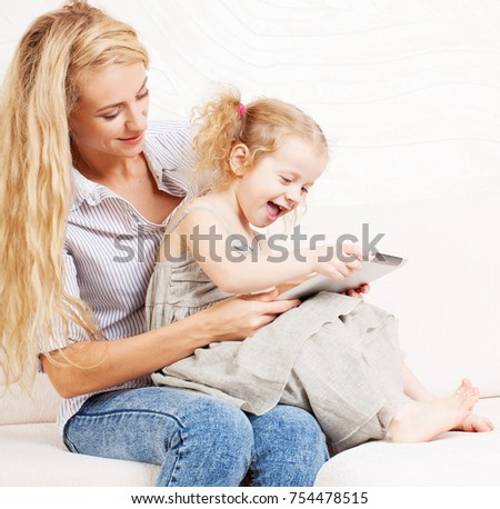 Family wiht tablet at sofa. Woman and baby with tablet computer. Mother and daughter at home on sofa