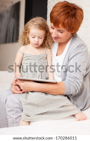 Family wiht tablet computer at sofa. Grandmother and little girl at home on sofa. Generation - stock photo