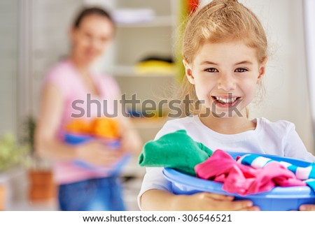 family with a basin full of laundry - stock photo