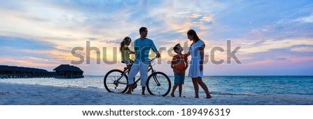 Family with a bike on tropical beach at sunset - stock photo