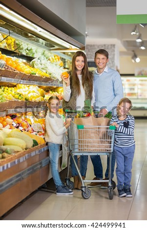Family with a cart in store - stock photo