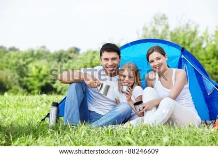 Family with a child in a tent on the nature - stock photo