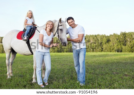 Family with a child on a horse - stock photo