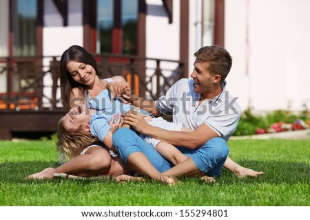 Family with a child playing on a lawn - stock photo