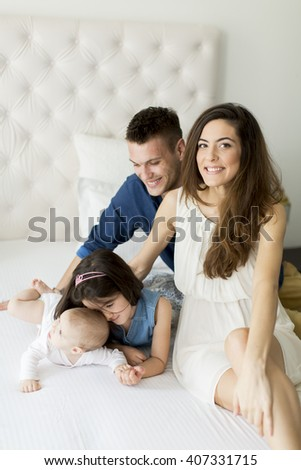 Family with a girl and a baby on the bed