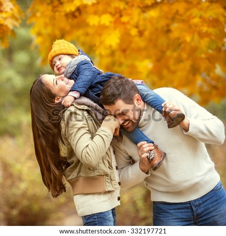 Family with a small daughter happy in autumn park  - stock photo