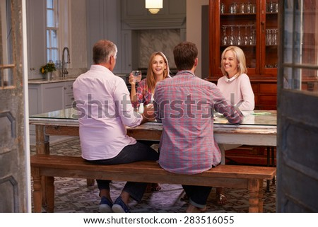 Family With Adult Offspring Enjoying Meal At Home Together - stock photo