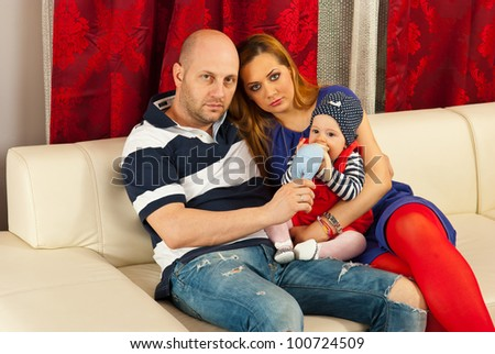 Family with baby girl sitting on couch in their living room