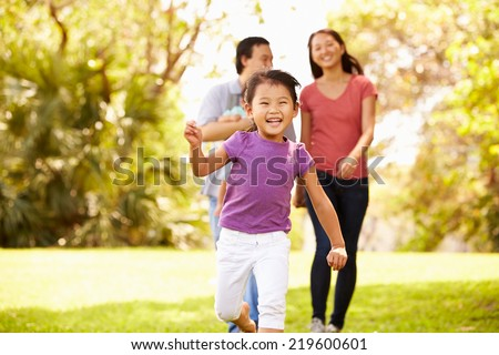 Family With Baby In Carrier Walking Through Park - stock photo