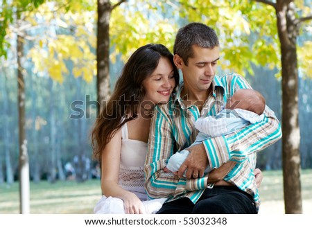 family with baby in  in autumn park - stock photo