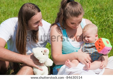 family with baby in meadow