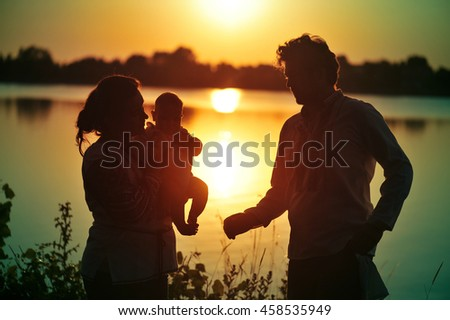 Family with baby silhouette at sunset, father holding a baby in her arms