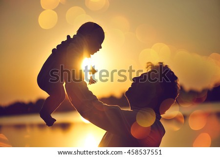 Family with baby silhouette at sunset, father holding a baby in her arms.