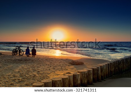 Family with bicycles on the Baltic Sea at sunset - stock photo
