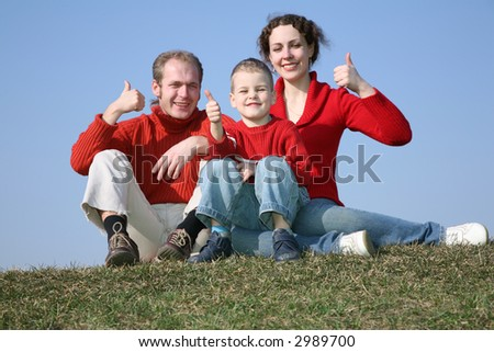 family with bou OK gesture on meadow - stock photo