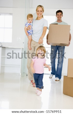 Family with box moving into new home smiling - stock photo