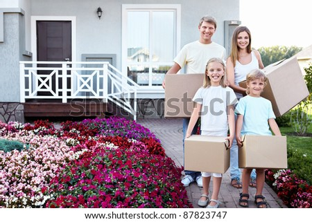 Family with boxes in the house - stock photo