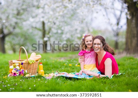 Family with children enjoying picnic in spring garden. Parents and kids having fun eating lunch outdoors in summer park. Mother, father, son and daughter eat fruit and sandwiches on colorful blanket. - stock photo