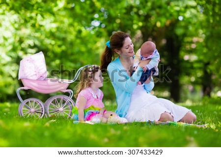 Family with children enjoying picnic outdoors. Mother with newborn baby and toddler child relax in a park. Little girl playing with toy stroller. Mom and kid play with infant boy. Kids birthday party. - stock photo
