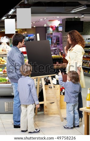 Family with children in shop look at an empty board - stock photo