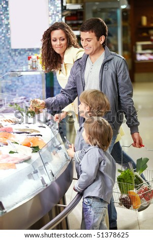 Family with children near to seafood in shop - stock photo
