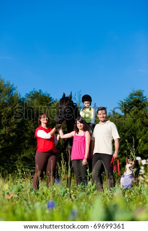 Family with children posing with a horse, one child riding the animal - stock photo