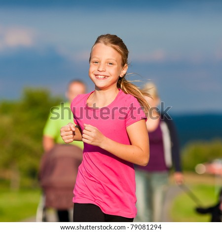 Family with children (the baby lying in a baby buggy) walking down a path outdoors, one kid is running ahead - stock photo
