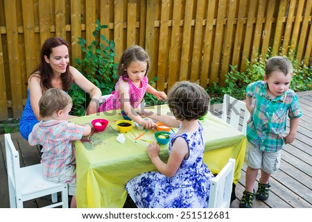 Family with children together painting and decorating eggs outside during the spring season in a garden setting.  Smiling mother looks on as her kids color dye their Easter eggs.  Part of a series.    - stock photo
