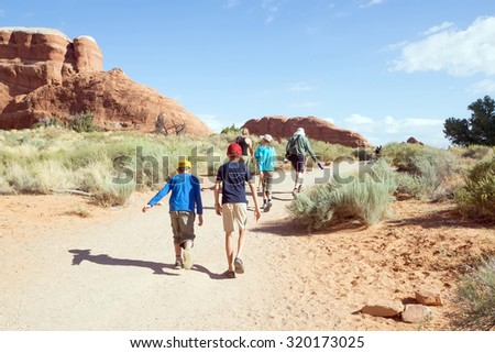 Family with children walking along the trail in Arches National Park, Utah - stock photo