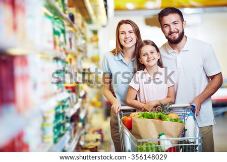 Family with chopping cart during shopping at vegetable supermarket - stock photo