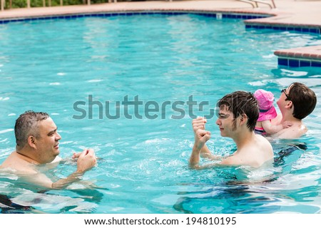 Family with cute baby girl faving fun in outdoor swimming pool on hot summer day. - stock photo