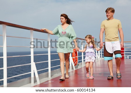 family with daughter walking on cruise liner deck, full body, looking left - stock photo