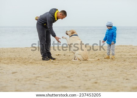family with dog on the beach in fall time - stock photo