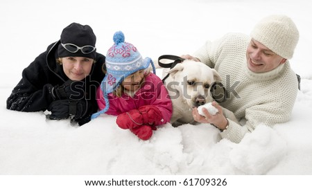 Family with dog playing in snow
